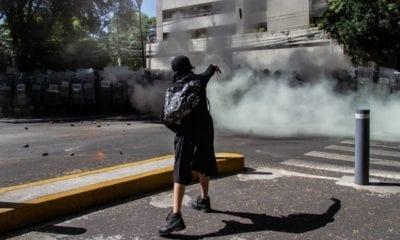 Una joven lanza piedras a elementos de la policía mientras protestaban frente a la casa en representación de Jalisco. Foto: Cuartoscuro